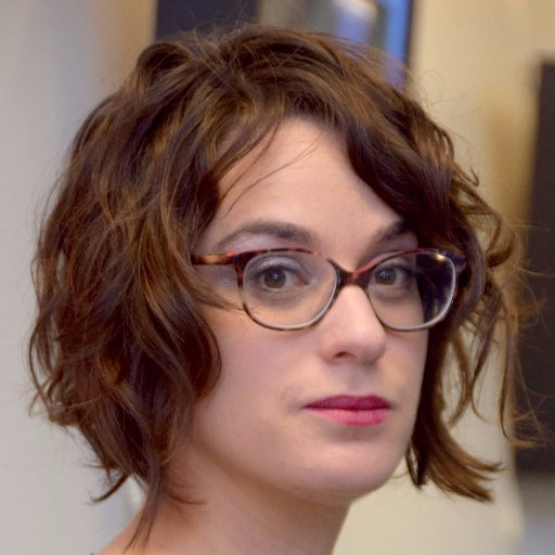 Kathy Friedman wears glasses and has a wavy bob with medium-brown hair in this headshot image