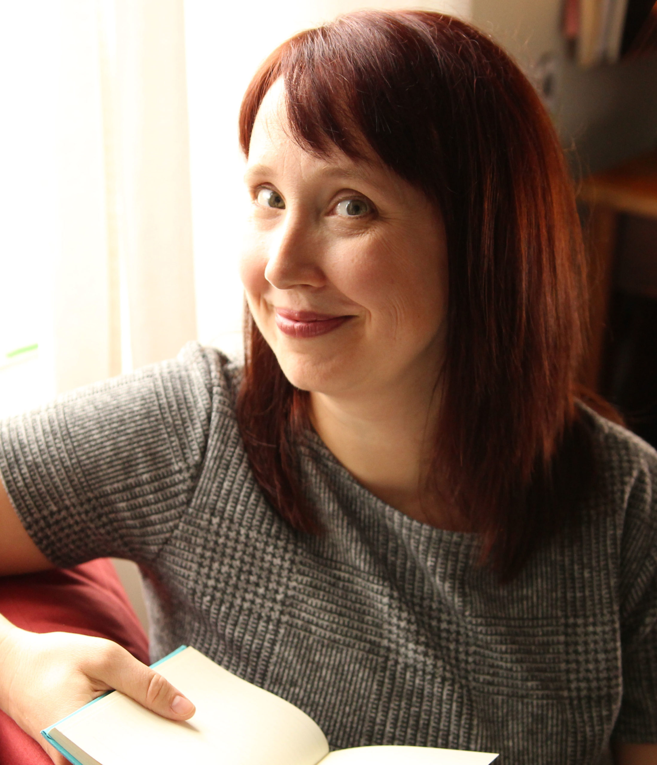 Rachel Thompson sitting at a pink chair, holding a book, looking at the camera.