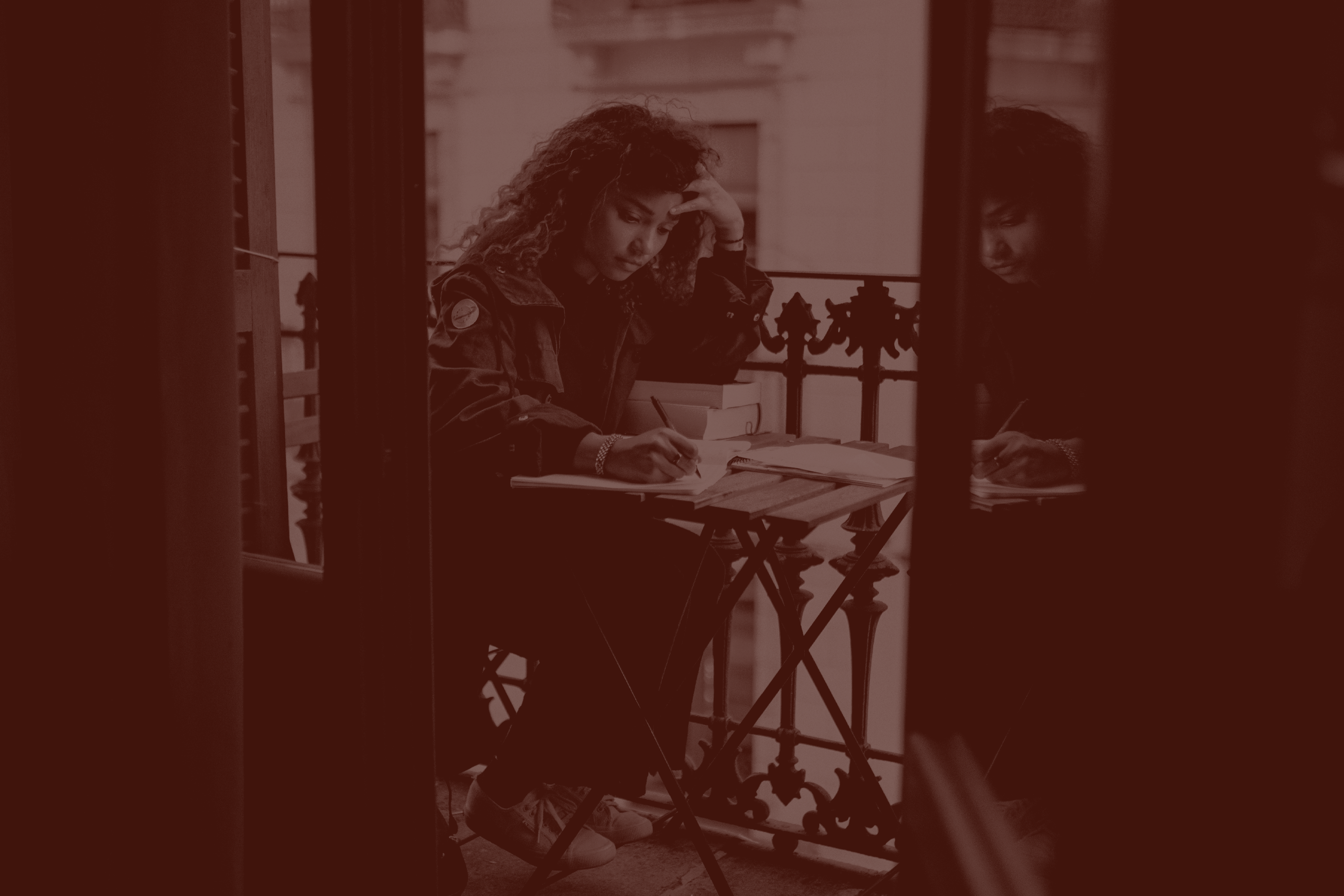 Woman writing on a balcony