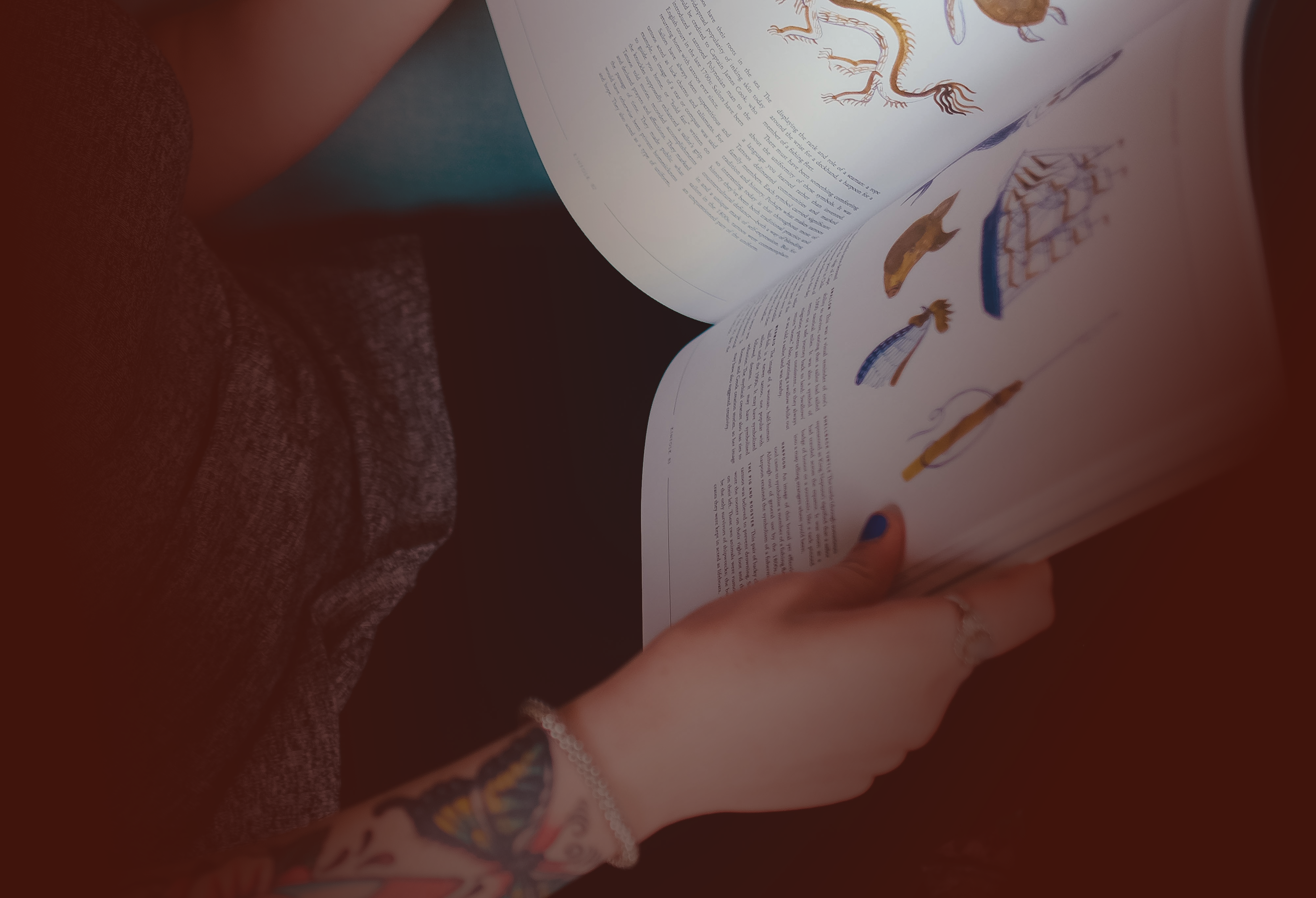 A person with arm tattoos and a bracelet holds a magazine open on their lap—only their lap is visible in the photo.