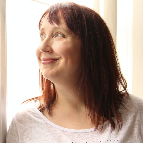 Rachel Thompson, slightly smiling with medium, reddish-brown hair, looking up out a window.