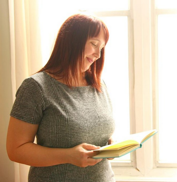 Rachel Thompson in front of a window looking down at a book, slightly smiling. She has medium-length reddish-brown hair with bangs.