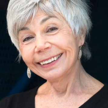 Jane Munro has short grey hair and wears earrings and a black top.