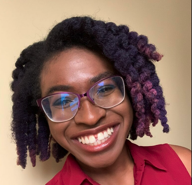 Léonicka Valcius has black and purple-tipped braided hair, wears glasses and a red collared shirt.