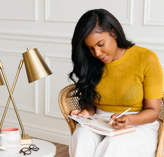 A woman in a yellow sweater shirt sits in a chair and writes in a planner.