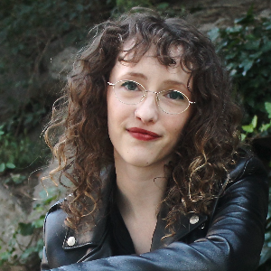 Lilly Dancyger has long curly hair and wears gold-metal framed glasses, red lipstick, and a leather jacket.
