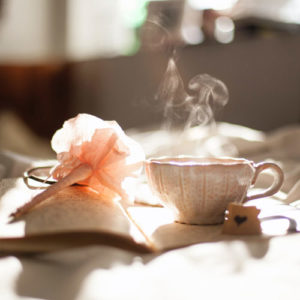 Teacup steaming in morning light on a notebook with written pages and with a pink flower-pen on top.