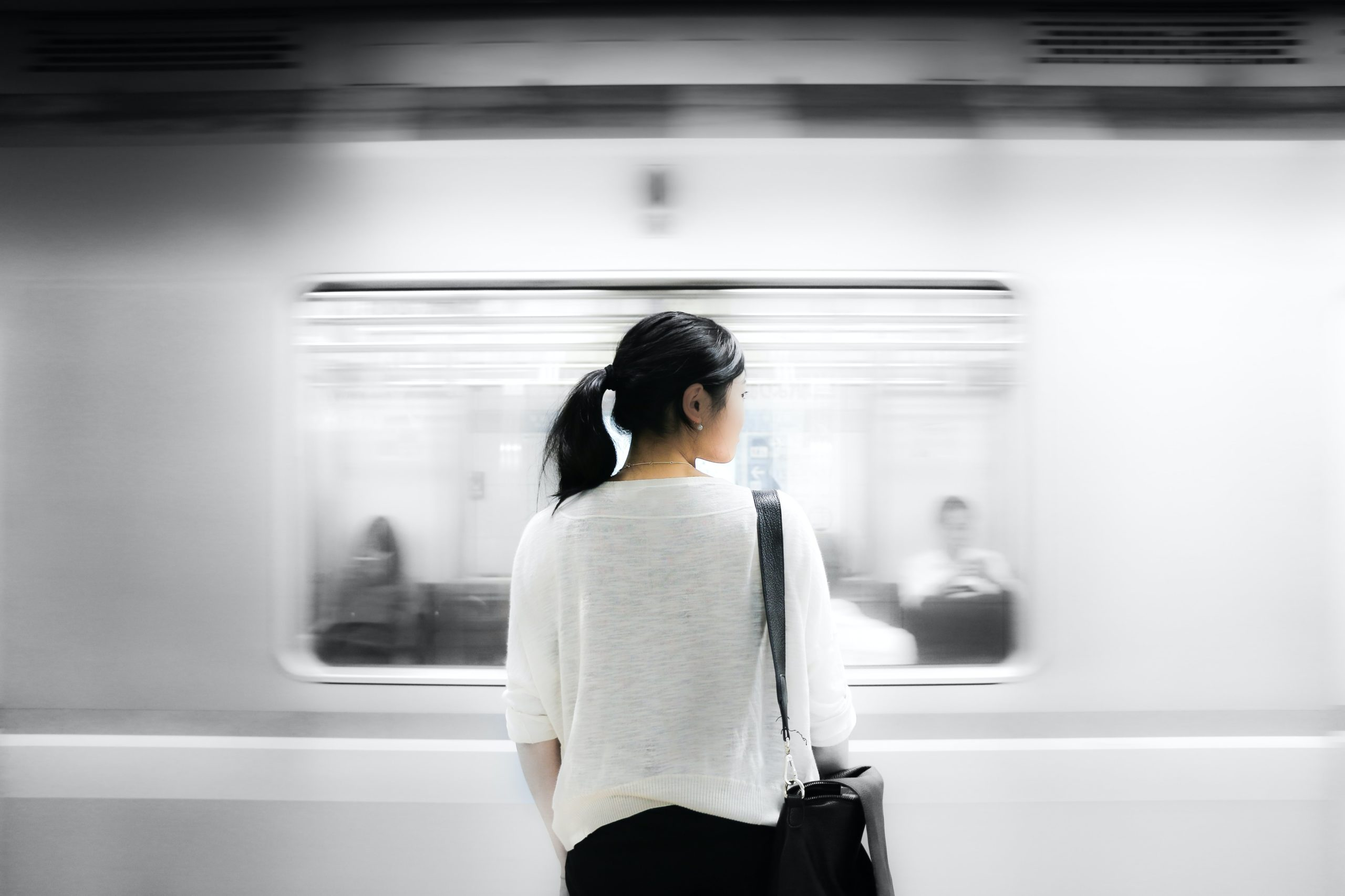 Woman in white with black hair in a pony tail and a black handbag stands in front of a quickly moving train.
