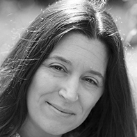Hannah Grieco has long dark hair parted in the middle in this black and white headshot.