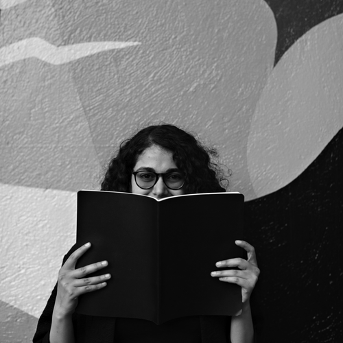 Woman with curly hair wearing glasses hiding behind a notebook.