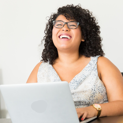 A woman laughs at her laptop. She has curly black hair and wears glasses.