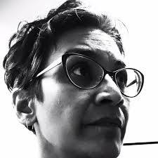 Mridula looks to the right of the camera, wears glasses, has a neutral expression, and short-cropped dark hair in this black and white photograph closeup of her face.