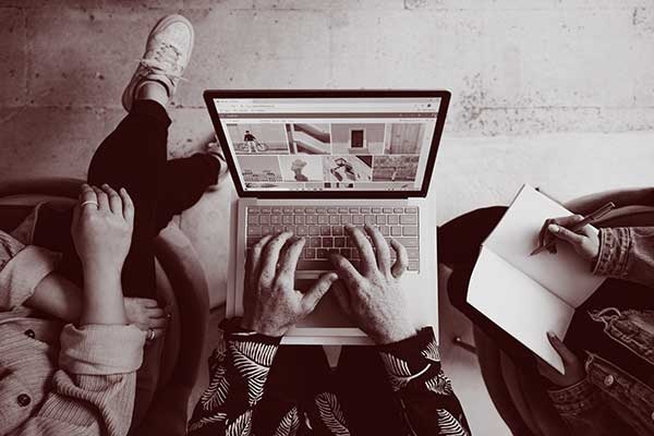 A photo taken from above three people whose arms you and legs you can see. One has fingers on a computer keyboard and the another has a pen with an open notebook, the third has an empty lap with legs crossed.