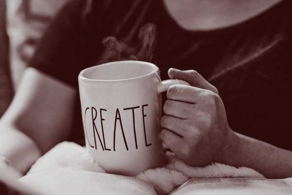 Close crop of a person holding a book and a cup with the word CREATE on it.